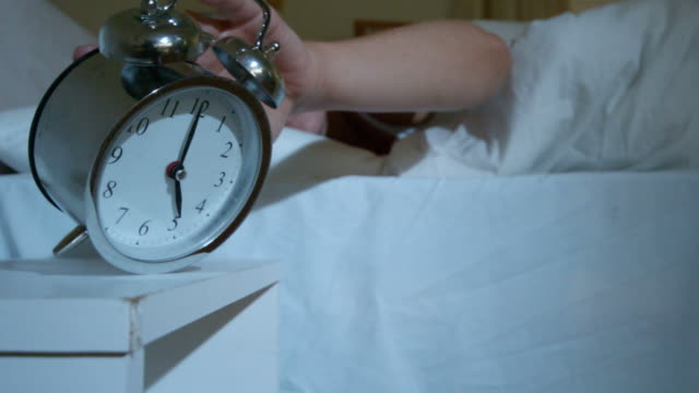 Blonde woman in bed knocking over alarm clock