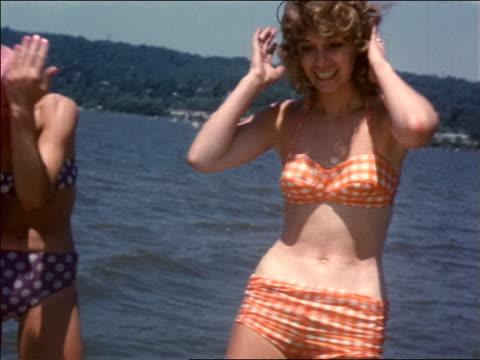 1966 blonde woman in bikini dancing + smiling by lake / home movie