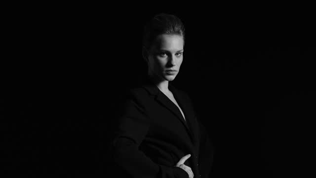 blonde woman in black jacket, holds her hands at her waist and turns face on camera. black and white video. - tights stock videos & royalty-free footage