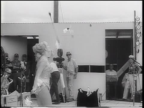 b/w 1967 blonde woman in costume twirling throwing burning batons in uso show / vietnam war - burning stock-videos und b-roll-filmmaterial