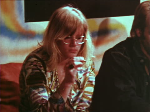 vídeos de stock e filmes b-roll de 1969 blonde woman in eyeglasses smoking joint at party / educational - hippie
