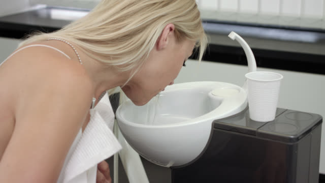 blonde woman in her 30s in a dentist's office spitting out water in the sink after receiving dental care treatment, in the background medical dental equipment. - spitting stock videos & royalty-free footage