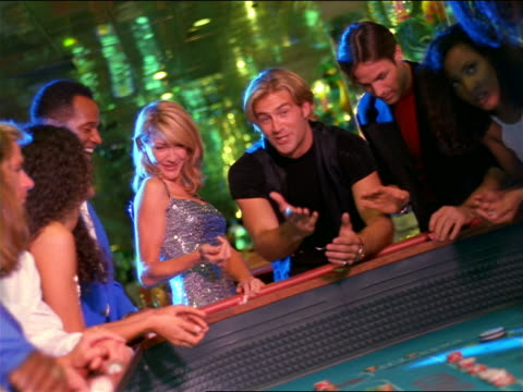 canted blonde woman in sequined dress rolling dice at craps table as cheering friends watch - craps stock videos & royalty-free footage
