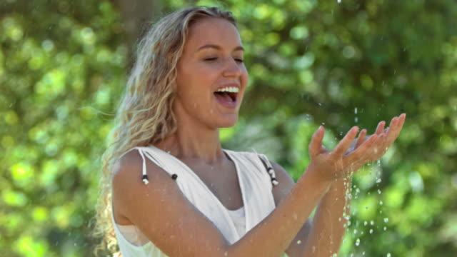 vídeos y material grabado en eventos de stock de blonde woman in slow motion catching water - manos ahuecadas