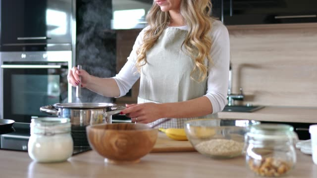 blonde woman in the kitchen making oatmeal for breakfast - cucina domestica video stock e b–roll