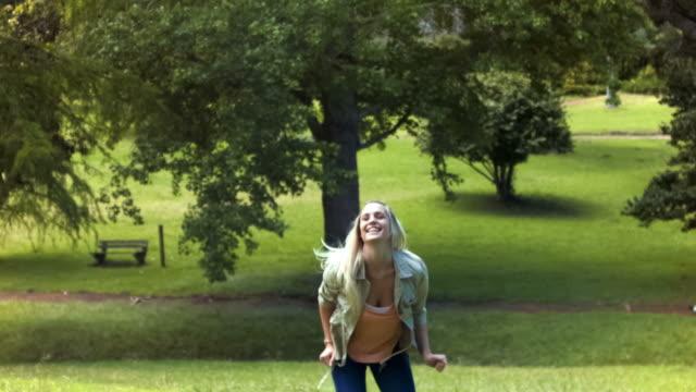 vidéos et rushes de blonde woman jumping in slow motion - bras en l'air