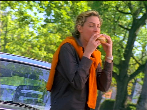 canted blonde woman leaning against car while eating hamburger + laughing - unhealthy eating stock videos & royalty-free footage