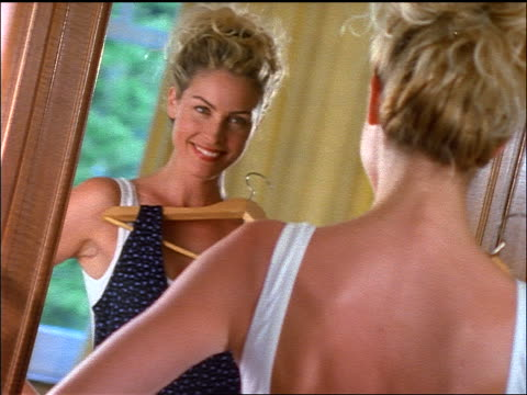 CANTED blonde woman looking in mirror while holding up dress / turns + laughs