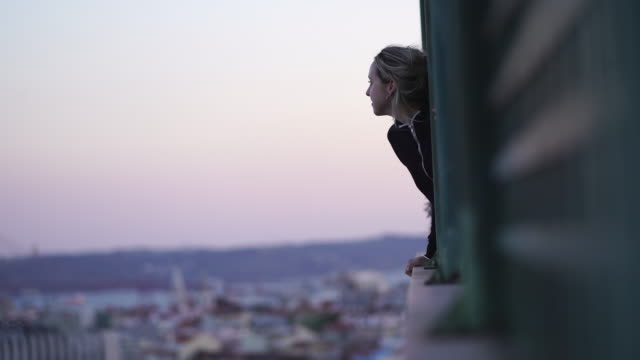 blonde woman looking out a balcony over lisbon - balcony stock videos & royalty-free footage