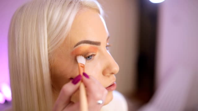 blonde woman make-up artist applying make up on eyes - side hustle stock videos & royalty-free footage
