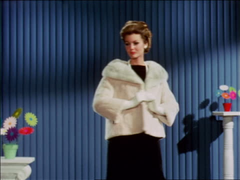 1968 blonde woman modeling muskrat collared jacket turning around indoors / industrial