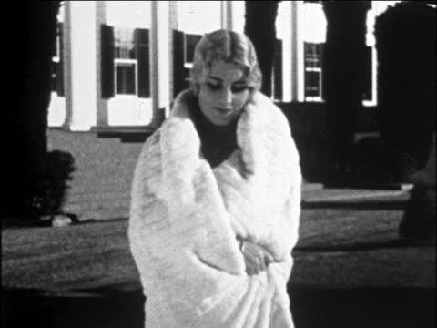 B/W 1929 blonde woman modeling white fur cape outdoors / newsreel