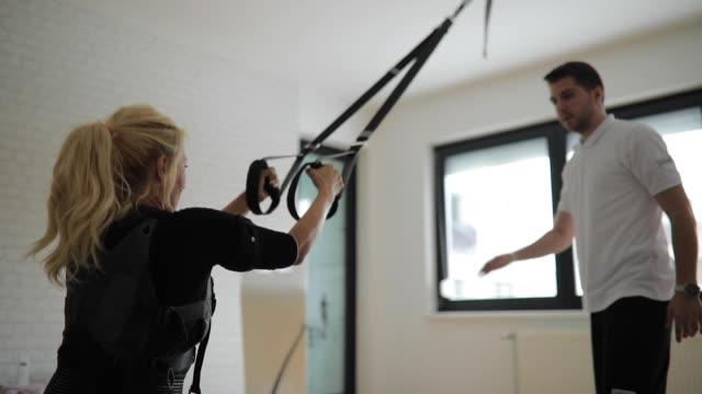 vídeos y material grabado en eventos de stock de mujer rubia en entrenamiento con entrenador personal - fisioterapia deportiva