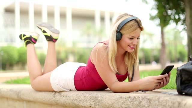 blonde woman on the mobile at park - nodding head to music stock videos & royalty-free footage