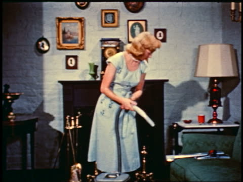 1950 blonde woman picking up metal tube vacuum attachment from sofa - stay at home mother stock videos & royalty-free footage