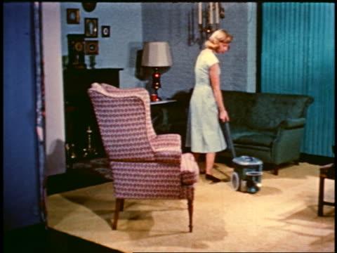 1950 blonde woman pulling small vacuum towards sofa
