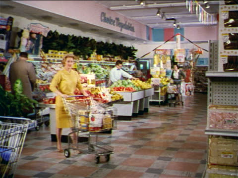 vidéos et rushes de 1962 blonde woman pushing shopping cart thru produce department of grocery store / industrial - caddie
