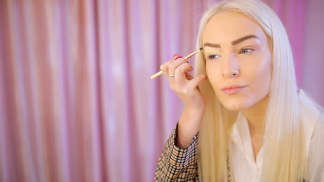 blonde woman putting make up on eyes - blogging stock videos & royalty-free footage