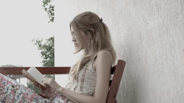 vidéos et rushes de femme blonde lire un livre - littérature