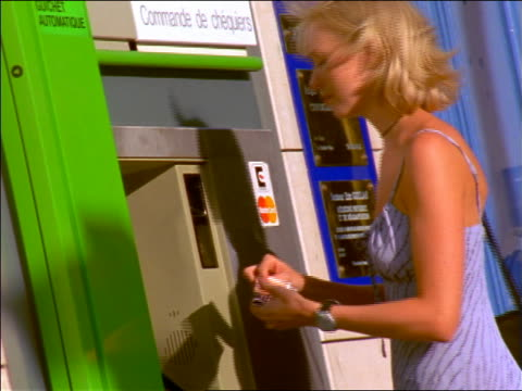 blonde woman removing card from atm / france - 1999年点の映像素材/bロール