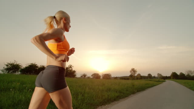 slo mo ts blonde woman running at sunset - running shorts stock videos and b-roll footage