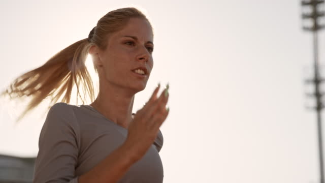 slo mo ds blonde woman running in the setting sun - athlete stock videos & royalty-free footage