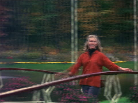 vidéos et rushes de 1966 blonde woman spinning + posing on footbridge in park / fountain in background / home movie - cheveux blonds
