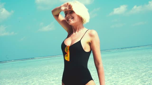 Blonde vrouw permanent in ondiep water, Maldiven