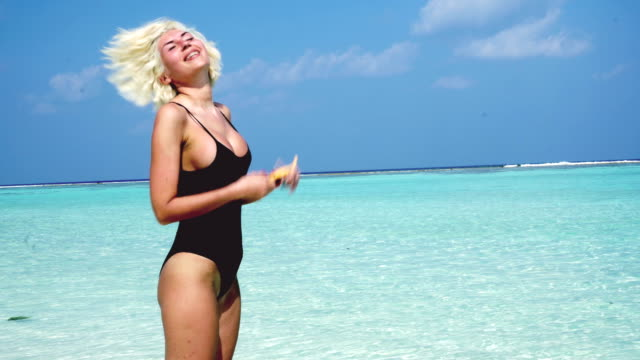 blonde woman standing at shallow water, maldives - tan stock videos and b-roll footage