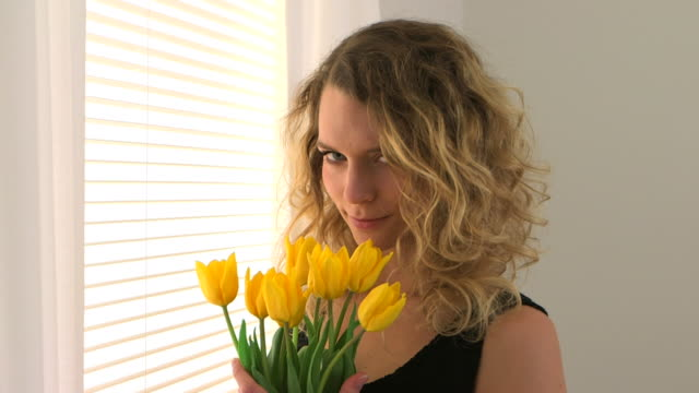 Blonde woman standing by a window with a bouquet of tulips