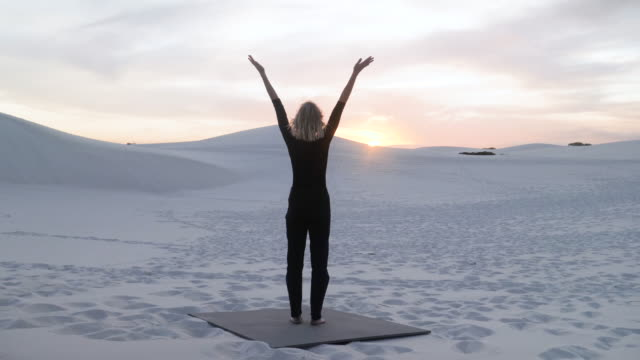 Blonde woman stretches at sunset, wide