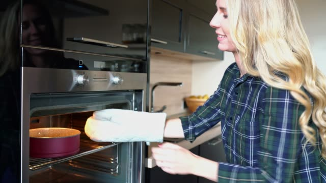 blonde woman taking a cake tray out of the oven - young women stock videos & royalty-free footage