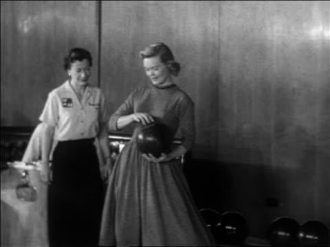 b/w 1955 blonde woman taking bowling ball from ball return + starting to bowl / educational - ten pin bowling stock videos & royalty-free footage