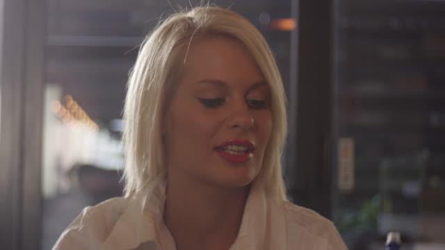 金髪女性話 4 k スローモーション - お食事デート点の映像素材/bロール