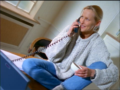 Blonde woman talking on telephone + holding coffee cup sitting on desk in home office