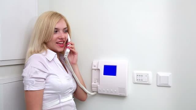 blonde woman talking on the video intercom - intercom stock videos and b-roll footage