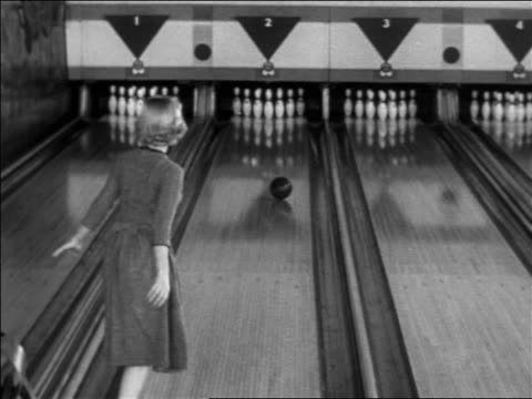 b/w 1955 rear view blonde woman throwing bowling ball + getting strike / excited - ボウリング点の映像素材/bロール