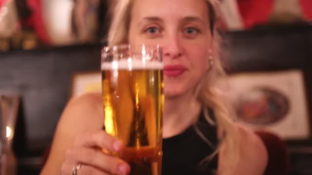 vídeos de stock, filmes e b-roll de mulher loura que brinda a câmera e o beber - brinde