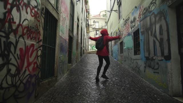 vidéos et rushes de femme blonde twirling dans une rue latérale - sac à dos