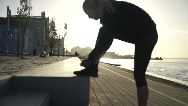 blonde woman tying her shoes then starting to run away from the camera - tie stock videos & royalty-free footage
