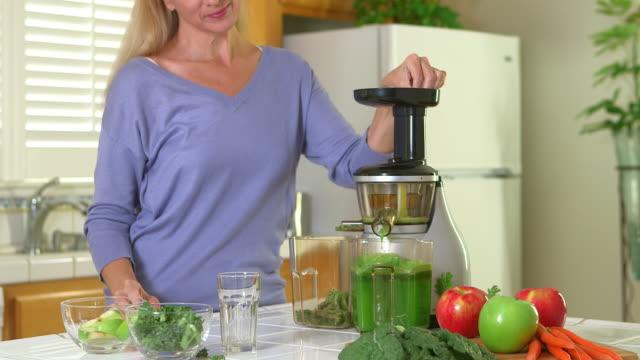 Blonde woman using juicing machine