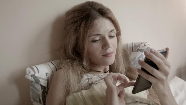 vidéos et rushes de femme blonde à l'aide de smartphone dans le lit - téléphone équipement de télécommunication