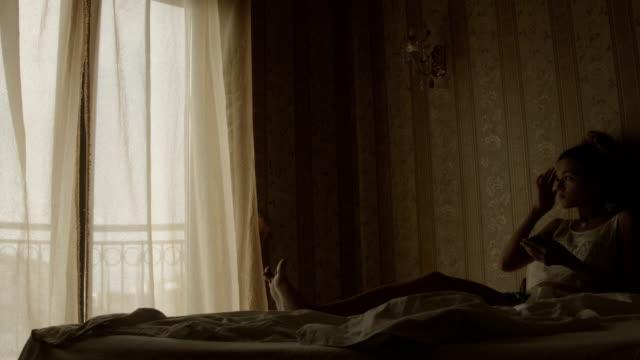 Femme blonde à l'aide de smartphone dans le lit