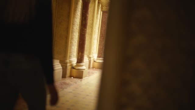 ブロンドの女性は華やかな寺のホールを歩いて - 建築上の特徴 アーチ点の映像素材/bロール