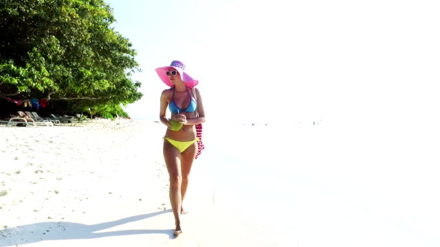 blonde woman walking on sandy beach and drinking coconut juice on maldives - bikini top stock videos & royalty-free footage