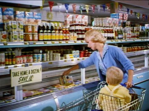 1962 blonde woman with baby in shopping cart taking boxes from freezer + putting them in cart in store