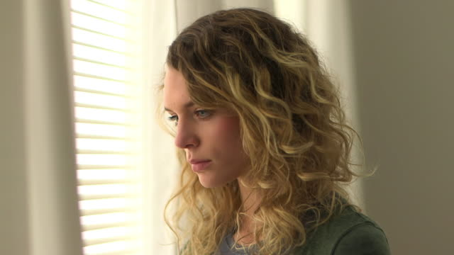 Blonde woman with curly hair standing by window