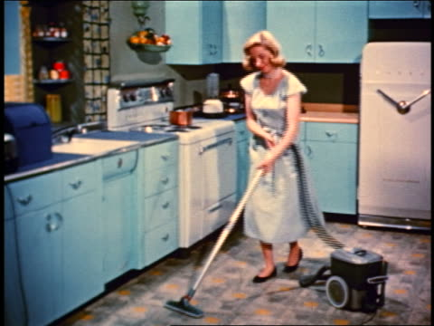 vídeos de stock e filmes b-roll de 1950 blonde woman with green vacuum cleaner vacuuming floor of kitchen - 1950