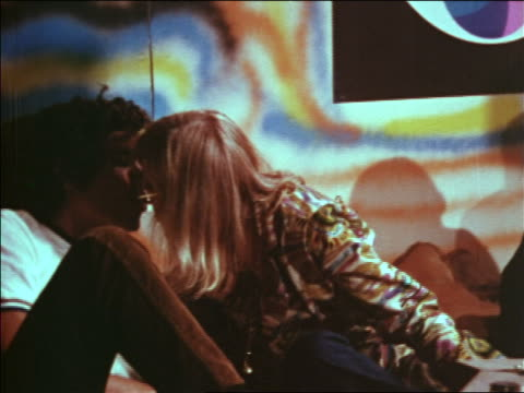 vídeos de stock e filmes b-roll de 1969 blonde woman with joint in mouth blowing smoke into man's mouth at party / zoom in to man - hippie