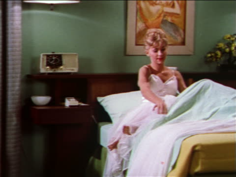 1959 blonde woman with nightgown getting into bed + pulling up covers + turning off light / industrial